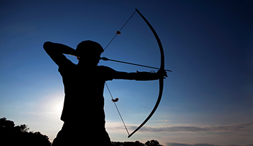 Silhouetted young man drawing back his bow to shoot